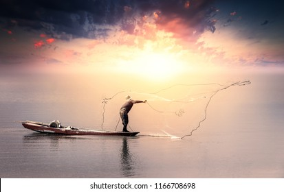 A fisherman is fishing by throw a net in the lake at sunset.