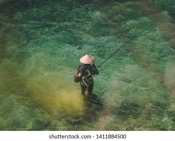 fisherman fishing in crystal blue water Bali