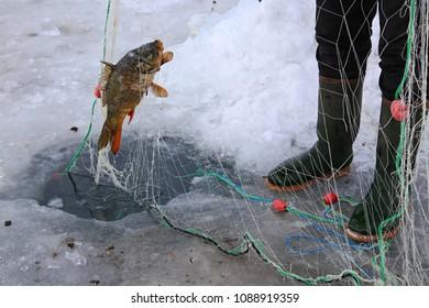 Fisherman is fishing on the frozen Cildir Lake (Cildir Golu), Ardahan nearby Kars, Turkey