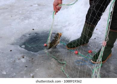 Fisherman is fishing on the frozen Cildir Lake (Cildir Golu), Ardahan nearby Kars, Turkey, differen angles