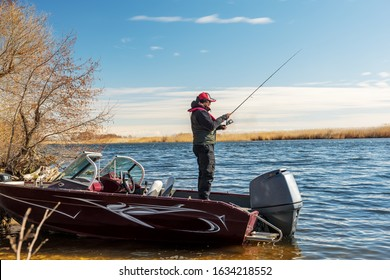 A fisherman is fishing on the river from a boat. Fisherman athlete. Male enthusiastic fishing in early spring on a wild river.