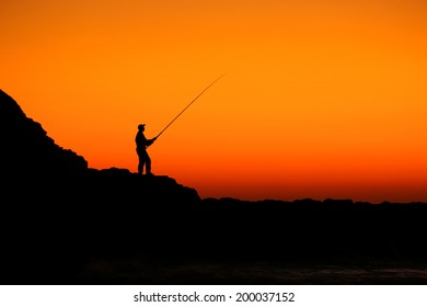 Fisherman fishing on the rocks early in the morning with the golden dawn sky shining behind him casting a beautiful silhouette.