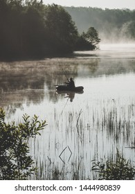Fisherman with a fishing rod on an inflatable boat fishing on the lake in early morning. Fog spreads on the lake where the lone fisherman is fishing on an inflatable boat