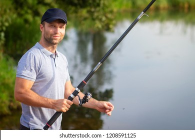 Fisherman with fishing rod on lake shore. Man catches of fish on river. Leisure activity. Hobby in outdoors. Fish hunter