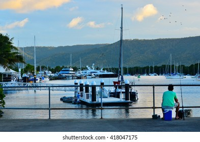 Fisherman fishing from the Sugar Wharf in Port Douglas in the far north of Queensland,  Australia.