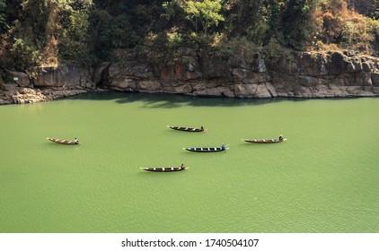 fisherman fishing traditional wood boats isolated at river image is taken at dwaki lake meghalaya india.