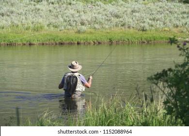 Fisherman flyfishing in river of Montana state