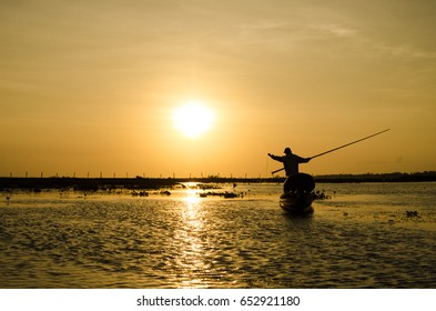 Fisherman going out on a small fishing boat in the early morning to put out fishing net in the local reservoir down the South of Thailand