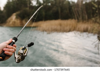 Fisherman hands with rod, spinning reel on the river bank. Man catching fish, pulling rod while fishing from lake or pond with text space. Fishing for pike, perch on lake or pond. Fishing day concept.