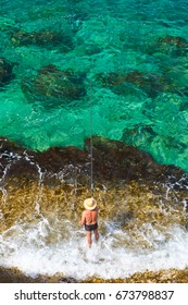 Fisherman with hat and with fishing rod is catching fish in the sea