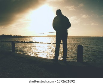 Fisherman with hat on the sea mole  with fish rod. Man standing above sea water and  fishing at sunset