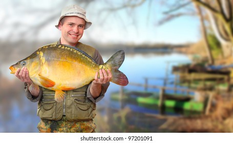 The fisherman with his big Carp at a beautiful lake in The South Bohemia. Czech Republic, Europe.