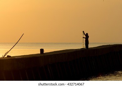 the fisherman with his net on the bridge in silhouette