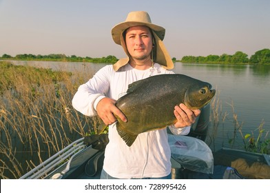 Fisherman holding a fish known as Pacu. Man using hat and white shirt holding a fish on board of a boat. Photo taken in Pantanal, Brazil.