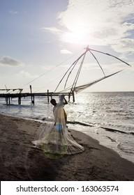 Fisherman holding a fishing net on the beach, Cochin, Kerala, India