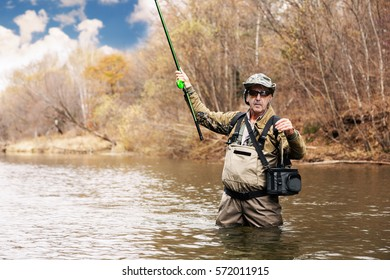 Fisherman holding a grayling caught in the river in autumn