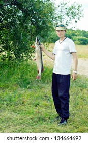 Fisherman Holding Large Pike. He just caught from the lake.
