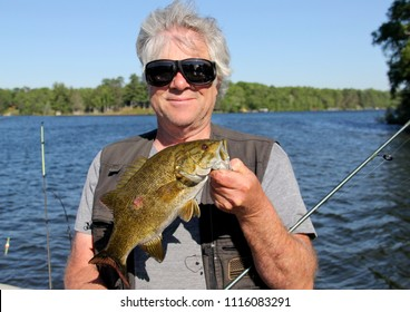 Fisherman holding a Smallmouth Bass with a blue sky and lake as the background