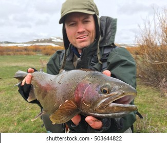 Fisherman holding trophy fish - Rainbow Trout (macro focus on head of fish)