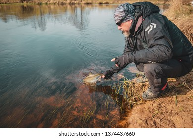 Fisherman holds asp in hand.