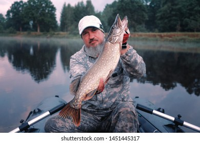 Fisherman holds a trophy pike.