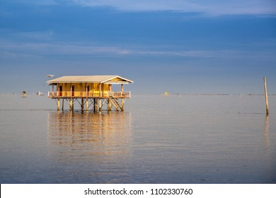 Fisherman house on the calm lake .Stilt houses built on the sea in Thailand