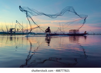 Fisherman of lake in action when fishing on twiligh