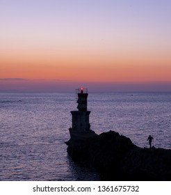 fisherman and lighthouse on the coast at sunset in Pasaia, Basque Country