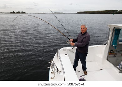 fisherman looks at you while catching a fish