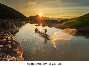 Fisherman of mekong river in action when fishing of sunrise