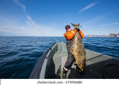 fisherman in the middle of the sea with a huge fish
