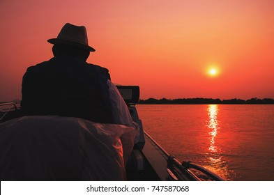 Fisherman navigating in his boat at sunset on Paraguai river, in Pantanal - Brazil. Contrasting colors on a colorful golden hour sunset and the sun reflecting on water.