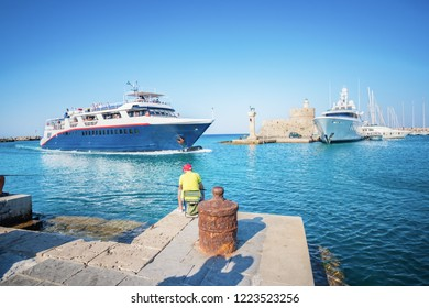 Fisherman near entrance into Mandraki harbor in City of Rhodes (Rhodes, Greece)