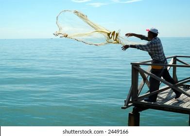 fisherman netting fish at a jetty