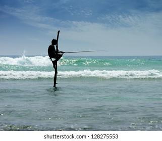 fisherman in ocean . Traditional sri lankan sit fisherman