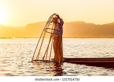 Fisherman on bamboo boat is catching fish by traditional handmade net. Photo made on Inle lake, Myanmar (Burma).