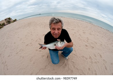 Fisherman on the beach through fish-eye lens