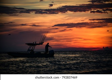 Fisherman on the boat catching fish at beautiful colorful sunset in paradise in Florida.