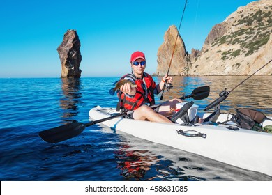 Pescador en el barco kayak muestra peces capturados en el mar. Joven haciendo kayak pescando cebo cerca de la isla con montañas.
