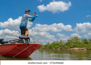 Fisherman on boat make a cast by fishing rod at wild river