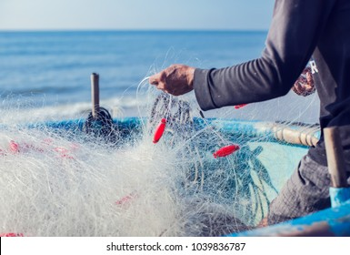 fisherman on boat with net in hands