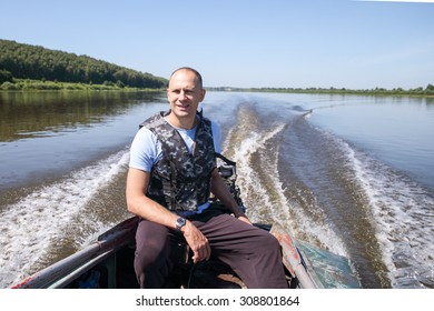 Fisherman on boat rides in big river
