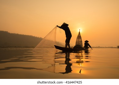 fisherman on boat with sunrise background, the Mekong River in Thailand.