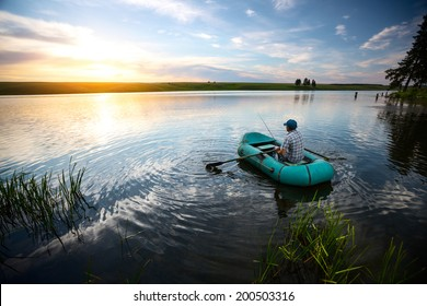 Fisherman on the boat watching sunset over the pond