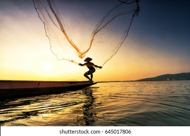Fisherman on a fishing boat in a river at sunset,Thailand