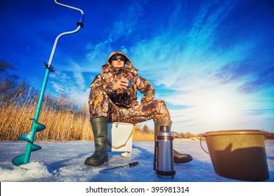 Fisherman on a lake at winter