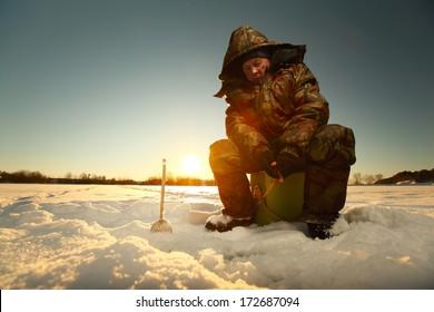 Fisherman on a lake at winter sunny day