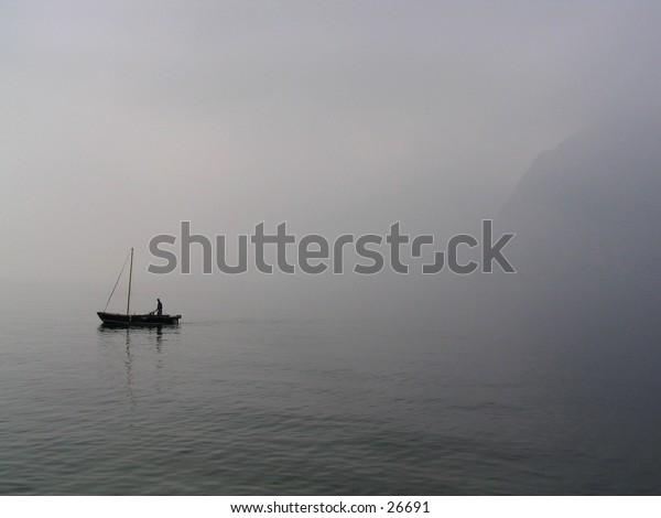 Fisherman on a misty lake