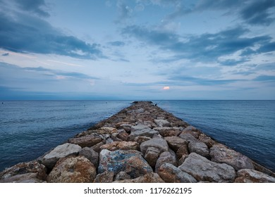 Fisherman on the pier by the sea in the morning light before sunrise with cloudy blue sky