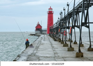 A fisherman on the pier of The Grand Haven South Lighthouse on the eastern shore of Lake Michigan. in late winter.